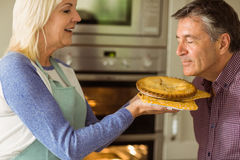 Mature blonde holding fresh pie with husband kissing her Royalty Free Stock Photos