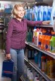 Woman choosing detergent. Mature blonde woman choosing detergent in  supermarket Stock Images