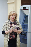 Mature blonde woman counting money near ATM Royalty Free Stock Photo