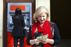 Mature blonde woman counting money near ATM Royalty Free Stock Image