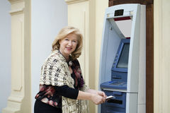 Mature blonde woman counting money near ATM. Mature blonde woman counting money near automated teller machine in shop Royalty Free Stock Photography