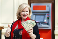 Mature blonde woman counting money near ATM Stock Images