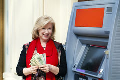 Mature blonde woman counting money near ATM Stock Photography