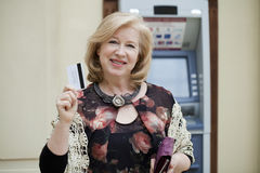 Mature blonde woman with credit card in hand near ATM Stock Photo