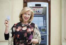 Mature blonde woman with credit card in hand near ATM Royalty Free Stock Photos