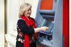 Mature blonde woman with credit card in hand near ATM Royalty Free Stock Photography