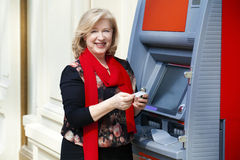 Mature blonde woman with credit card in hand near ATM Stock Images