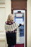 Mature blonde woman with credit card in hand near ATM Royalty Free Stock Image