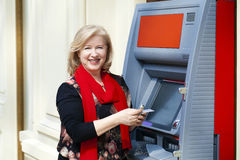 Mature blonde woman with credit card in hand near ATM Royalty Free Stock Photo