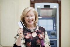 Mature blonde woman with credit card in hand near ATM Stock Photography