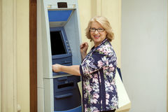 Mature blonde woman with credit card in hand near ATM Stock Image