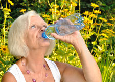 Mature, blonde woman drinking water. Royalty Free Stock Image