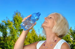 Mature, blonde woman drinking water. Stock Photo