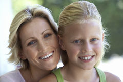 Mature blonde woman and girl (7-9) smiling, close-up, portrait Royalty Free Stock Photo