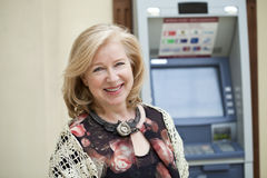 Mature blonde woman near ATM Royalty Free Stock Image