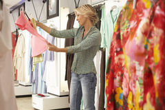 Mature blonde woman shopping in clothes shop, choosing between two different coloured tops, side view Royalty Free Stock Photography