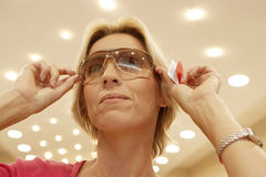 Mature blonde woman trying on pair of sunglasses in shop, smiling, close-up, low angle view Royalty Free Stock Photography