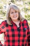 A mature blonde woman wearing a buffalo plaid flannel shirt red and black poses for a portrait in the Eastern Sierra Nevada. Mountains in California, on top of royalty free stock photography