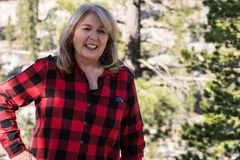 A mature blonde woman wearing a flannel shirt red and black poses for a portrait in the Eastern Sierra Nevada. A mature blonde woman wearing a plaid flannel royalty free stock images
