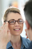 Mature blong woman trying on exeglasses Royalty Free Stock Image