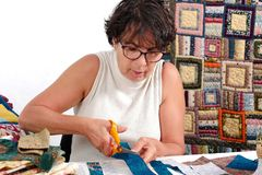Mature brunette woman cutting fabric for sewing patchwork Royalty Free Stock Photo