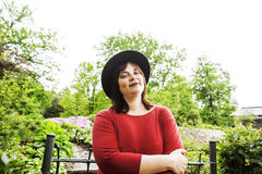 Mature brunette woman in green garden wearing hat, smiling, frie Royalty Free Stock Image