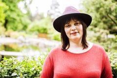 Mature brunette woman in green garden wearing hat, smiling, frie Stock Image