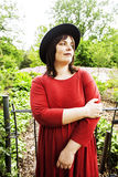 Mature brunette woman in green garden wearing hat, smiling, frie Royalty Free Stock Photo