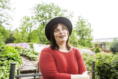 Mature brunette woman in green garden wearing hat, smiling, friendly welkoming, lifestyle people concept close up Stock Photo