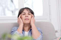 Mature brunette woman with  headache at home Stock Photos