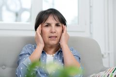 Mature brunette woman with  headache at home Stock Images