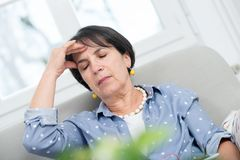 Mature brunette woman with  headache at home Royalty Free Stock Image