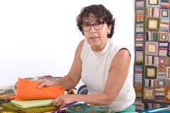 Mature brunette woman selected fabric sewing for patchwork Stock Images