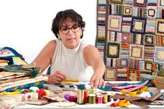 Mature brunette woman sewing patchwork Stock Photography