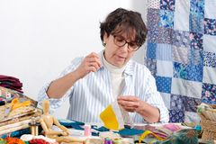 Mature brunette woman sewing patchwork. A mature brunette woman sewing patchwork Stock Photography