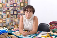 Mature brunette woman sewing patchwork. A pretty mature brunette woman sewing patchwork Royalty Free Stock Photography