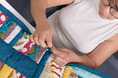 Mature brunette woman sewing patchwork. A pretty mature brunette woman sewing patchwork Royalty Free Stock Image