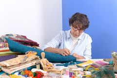 Mature brunette woman sewing patchwork. A pretty mature brunette woman sewing patchwork Stock Images