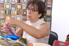 Mature brunette woman sewing patchwork. A pretty mature brunette woman sewing patchwork Royalty Free Stock Images