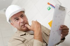 Mature builder with clipboard stock photos