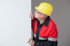 Mature builder peeping  out from behind the white wall Stock Photography
