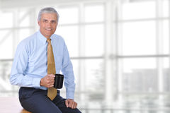 Mature Busimessman Sitting on Desk Royalty Free Stock Photos