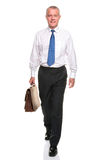 Mature businesman walking towards Stock Photos