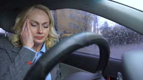 Mature business female suffering blood pressure disorder sitting car rainy day stock footage