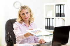 Mature business lady giving paper to colleague Stock Image