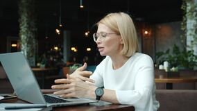 Mature business lady talking online using laptop computer in restaurant