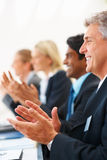 Mature business man clapping hands at a seminar Stock Images