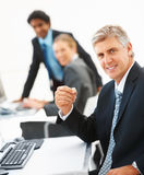 Mature business man with colleagues at the back Royalty Free Stock Image
