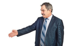 Mature business man gesture handshake. Mature business man standing in semi profile and gesturing handshake isolated on white background Stock Photos