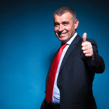 Mature business man making the ok sign. Mature business man making the ok thumbs up hand sign on blue background stock photo